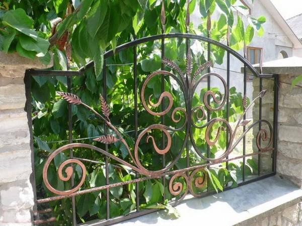 Забор из кирпича и ковки с растительным узором