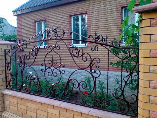 Забор из кирпича и ковки в палисаднике